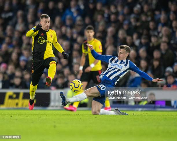 BRIGHTON ENGLAND FEBRUARY Watford's Gerard Deulofeu is tackled by Brighton Hove Albion's Solly March during the Premier League match between Brighton...