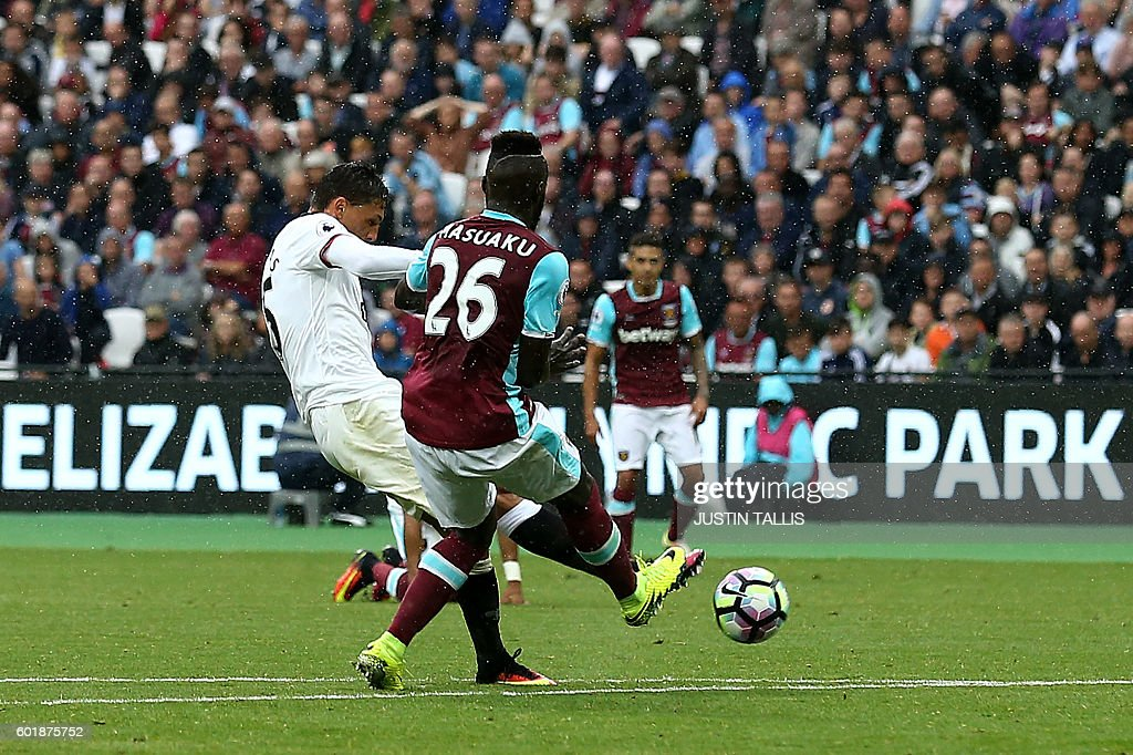 Watford's German-born Greek midfielder José Holebas (L) scores his team's fourth goal during the English Premier League football match between West Ham United and Watford at The London Stadium, in east London on September 10, 2016. / AFP / JUSTIN TALLIS / RESTRICTED TO EDITORIAL USE. No use with unauthorized audio, video, data, fixture lists, club/league logos or 'live' services. Online in-match use limited to 75 images, no video emulation. No use in betting, games or single club/league/player publications. /