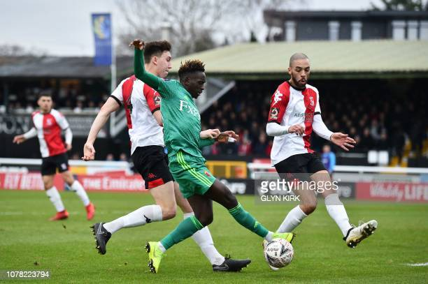 Watford's GuineaBissauanborn Portuguese midfielder Domingos Quina takes on Woking's English defender Jack Cook and Woking's English midfielder...
