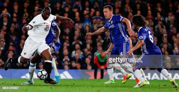 Watford's Italian striker Stefano Okaka shoots past Chelsea's English defender John Terry and Chelsea's Dutch defender Nathan Ake to score their...