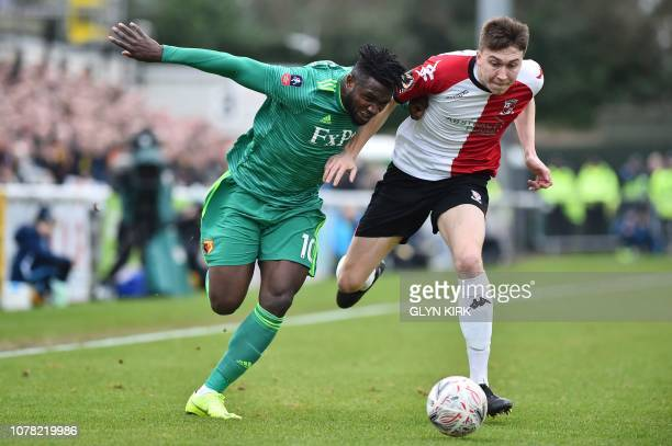 Watford's Nigerian striker Isaac Success battles with Woking's English defender Jack Cook during the English FA Cup third round football match...