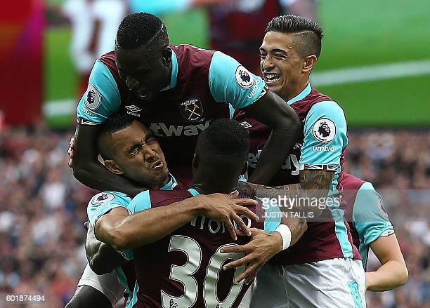 Watford's Romanian goalkeeper Costel Pantilimon is congratulated by teammates West Ham United's French midfielder Dimitri Payet and West Ham United's...