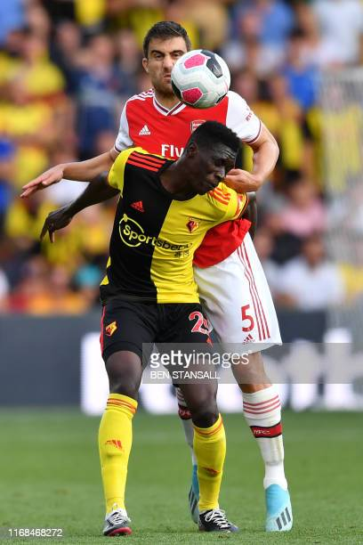Watford's Senegalese midfielder Ismaila Sarr vies with Arsenal's Greek defender Sokratis Papastathopoulos during the English Premier League football...