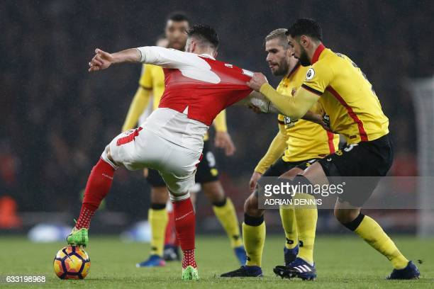 Watford's Uruguayan defender Miguel Britos tugs on the shirt of Arsenal's French striker Olivier Giroud during the English Premier League football...