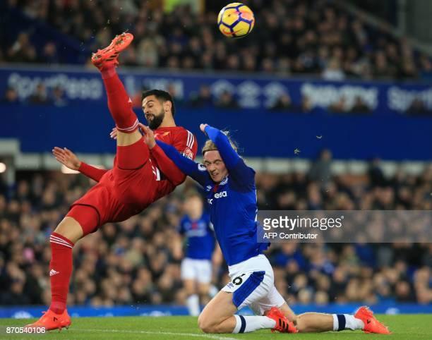 TOPSHOT Watford's Uruguayan defender Miguel Britos vies with Everton's English midfielder Tom Davies during the English Premier League football match...