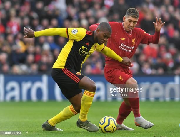 Watford's Zaireborn Belgian defender Christian Kabasele vies with Liverpool's Brazilian midfielder Roberto Firmino during the English Premier League...