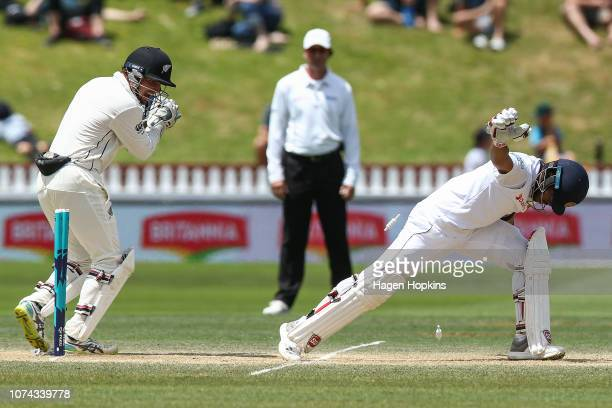 Watling of New Zealand removes the bails while Kusal Mendis of Sri Lanka stretches for the crease during day four of the First Test match in the...
