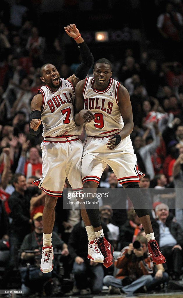 C.J. Watson #7 and Loul Deng #9 of the Chicago Bulls celebrate after Watson hit a three-point shot to tie the game in regulation against the Miami Heat at the United Center on April 12, 2012 in Chicago, Illinois. The Bulls defeated the Heat 96-86 in overtime.