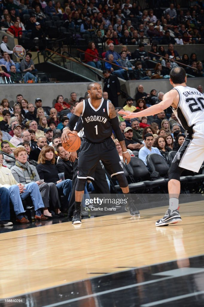 C.J. Watson #1 of the Brooklyn Nets dribbles the ball against Manu Ginobili #20 of the San Antonio Spurs on December 31, 2012 at the AT&T Center in San Antonio, Texas.