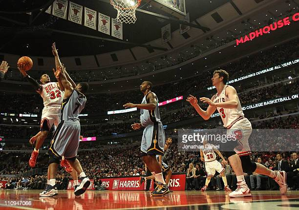 J Watson of the Chicago Bulls puts up a shot against Leon Powe of the Memphis Grizzlies at the United Center on March 25 2011 in Chicago Illinois The...
