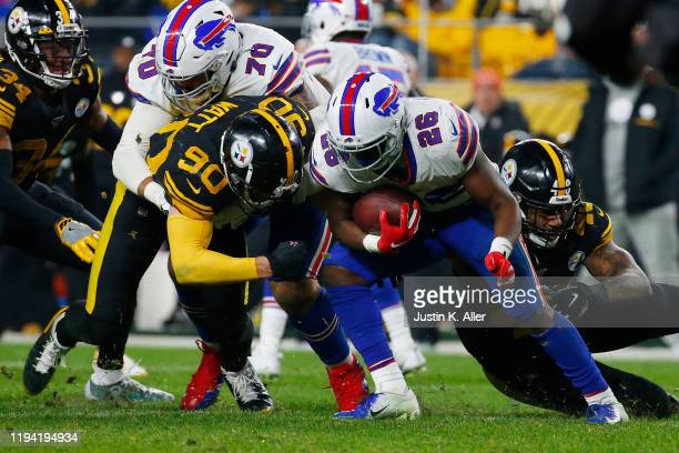 Watt and Bud Dupree of the Pittsburgh Steelers tackle Devin Singletary of the Buffalo Bills during the first half in the game at Heinz Field on...