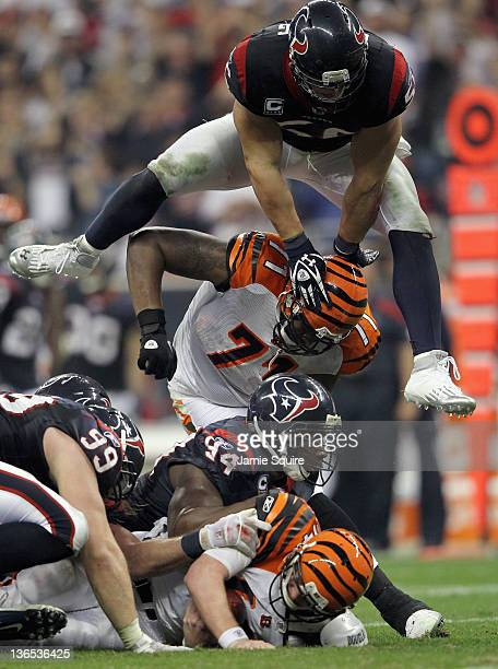JJ Watt Antonio Smith and Brian Cushing of the Houston Texans pile on Andy Dalton of the Cincinnati Bengals on a defensive sack during their 2012 AFC...
