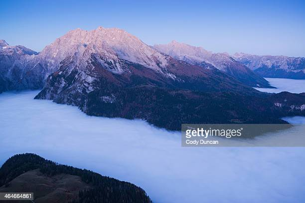 watzmann (2713m) rises above fog inversion layer at dawn, viewed from summit of jenner, berchtesgaden national park, bavaria, germany - berchtesgaden national park stock photos and pictures