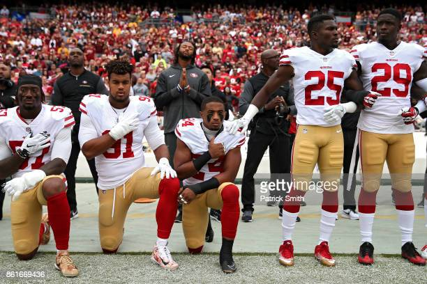 Waun Williams Arik Armstead and Eli Harold of the San Francisco 49ers kneel while holding their hands over their chest during the national anthem...
