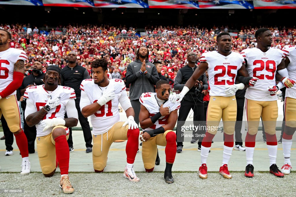 K'Waun Williams #24, Arik Armstead #91 and Eli Harold #57 of the San Francisco 49ers kneel while holding their hands over their chest during the U.S. national anthem before playing against the Washington Redskins at FedExField on October 15, 2017 in Landover, Maryland.
