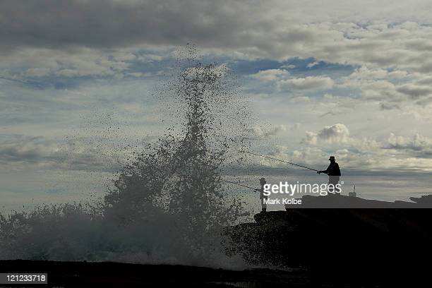A wave breaks on the rocks in front of fishermen at Cape Bank in La Perouse on February 20 2011 in Sydney Australia The practice of fishing from rock...