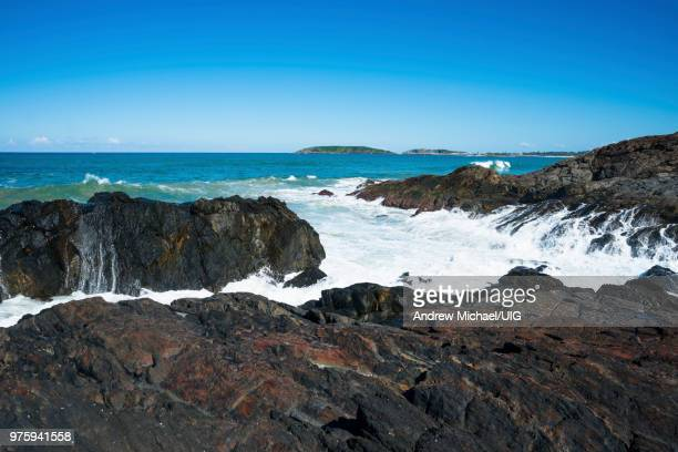 A wave crashes against the rocks at Macauleys Headland, Coffs Harbor coast, Australia.