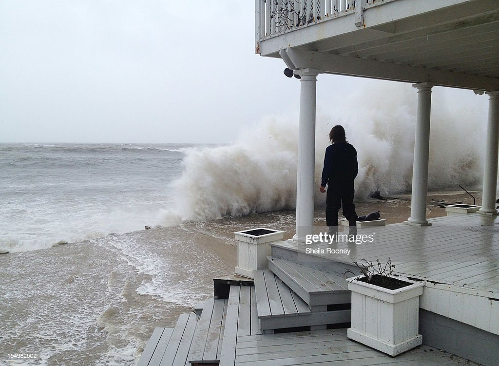 A wave crashes against the shore while person stands on a porch as Hurricane Sandy moves up the coast October 29, 2012 in Montauk, New York. Sandy, which has already claimed over 50 lives in the Caribbean, is predicted to bring heavy winds and floodwaters to the mid-Atlantic region.