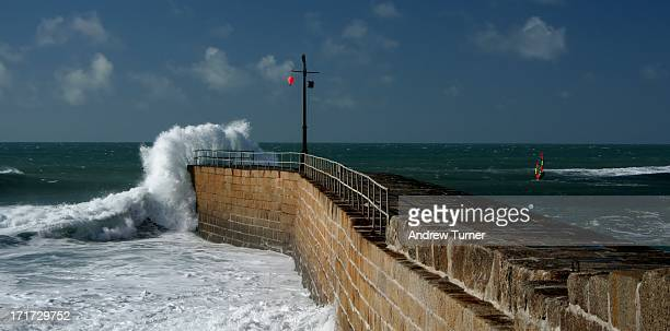 CONTENT] A wave crashes into the Breakwater at Porthleven as a windsurfer looks on