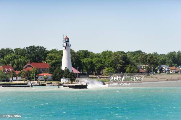 a wave crashes near the lighthouse at fort gratiot, mi - ポートヒューロン ストックフォトと画像