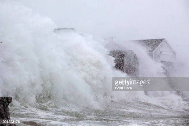 A wave crashes over a homes on Lighthouse Rd as a massive winter storm begins to bear down on the region on January 4 2018 in Scituate Massachusetts...