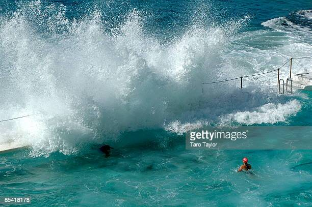 A wave crashes over swimmer in the Bondi pool