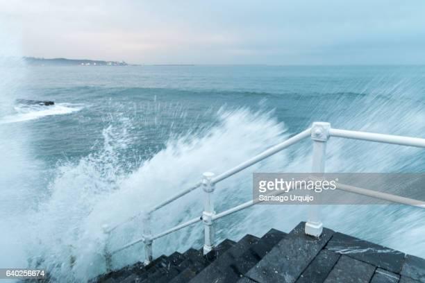 Wave crashing against the Gijon waterfront