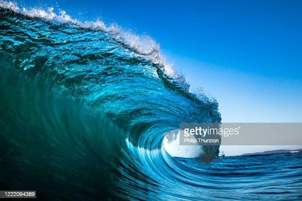 onda che si schianta nell'oceano con il cielo blu - onda foto e immagini stock