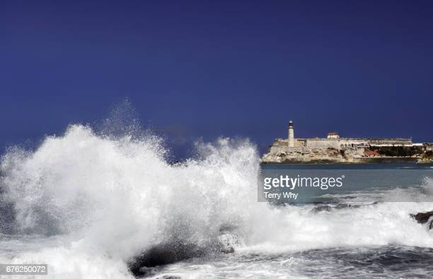 wave crashing on coast. Central Havana,Cuba.Castillo de San Salvador de la Paunta, in background