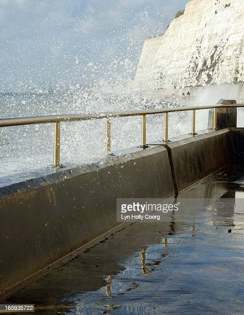 wave crashing over metal railings - lyn holly coorg stock pictures, royalty-free photos & images