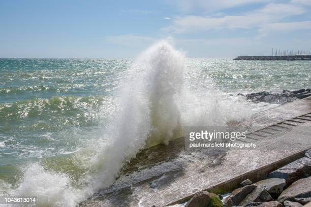 wave crashing over sea wall on brighton coastline - retaining wall stock pictures, royalty-free photos & images