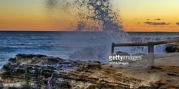 TORREDEMBARRA TARRAGONA SPAIN A wave hits the cliffs of the beach at Roc de San Gaíeta at sunset in Torredembarra Tarragona Spain