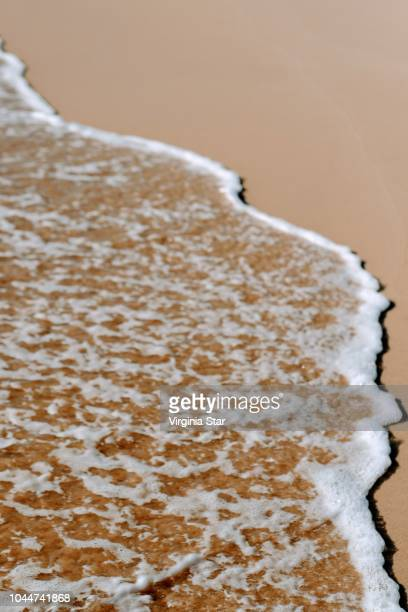 wave on a beach - water's edge stock pictures, royalty-free photos & images