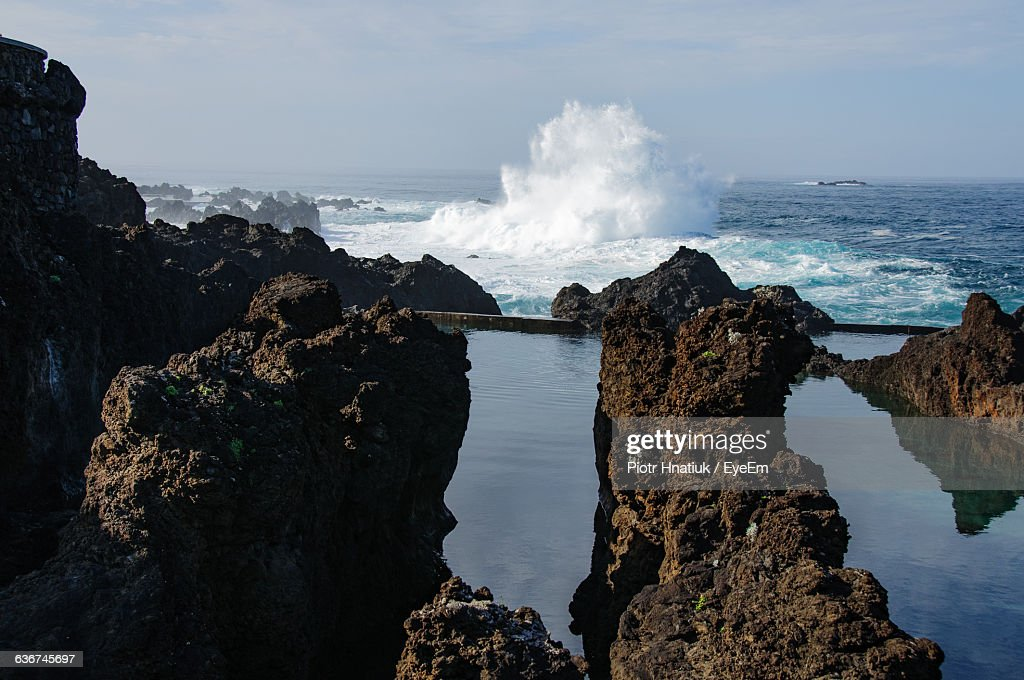 Wave Splashing In Sea With Rock Formation Against Sky : Stock Photo