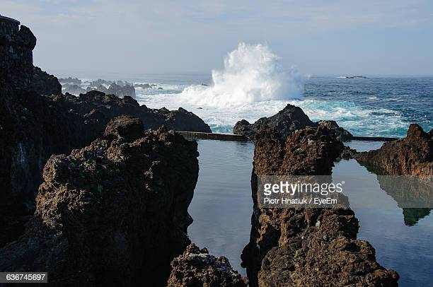 wave splashing in sea with rock formation against sky - piotr hnatiuk stock pictures, royalty-free photos & images