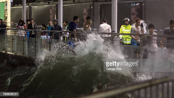Wave strikes a metal and glass railing in front of a crowd of onlookers in Tsim Sha Tsui during typhoon Usagi.