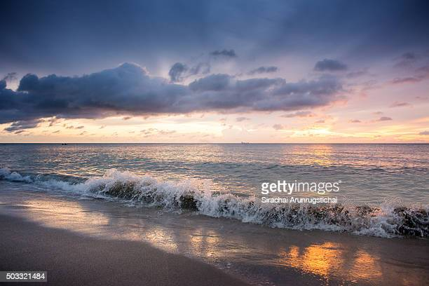 Wave washes over sandy beach under colourful sky at sunset