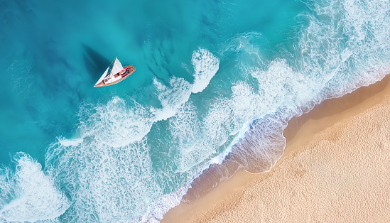 Waves and yacht from top view. Turquoise water background from top view. Summer seascape from air. Top view from drone. Travel-image 1127346848