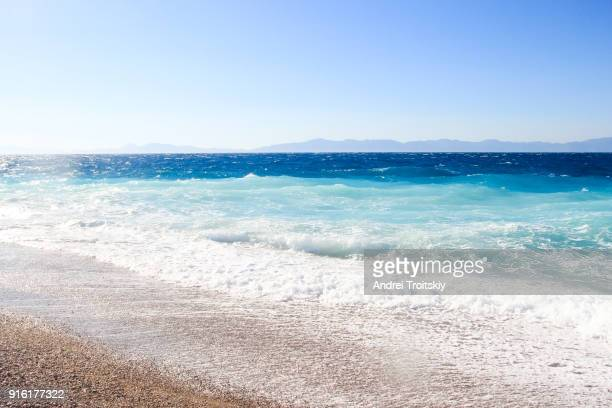 waves at the shore of aegean sea, rhodes, greece - dodecanese islands stock photos and pictures