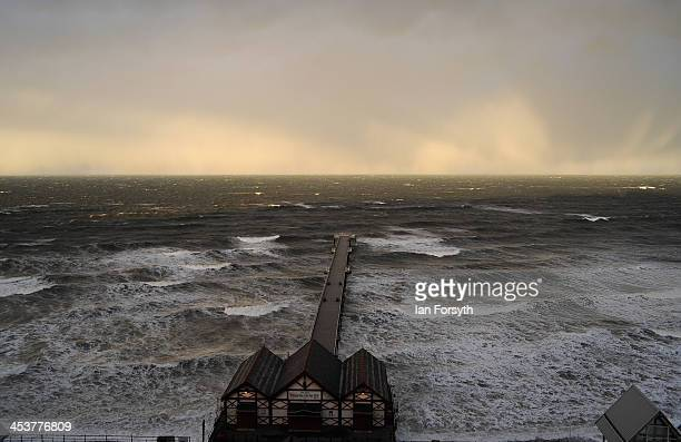 Waves begin to break against Saltburn pier during the storm surge on December 5 2013 in Saltburn United Kingdom Strong winds and big tides are...