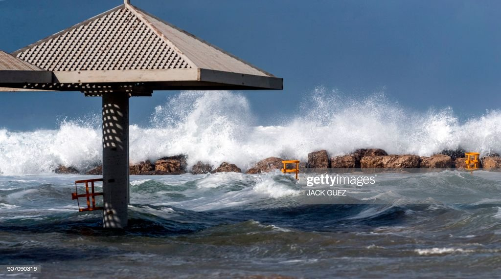 Waves break across the shore during a winter storm in the Israeli Mediterranean coastal town of Netanya, north of Tel Aviv, on January 19, 2018.