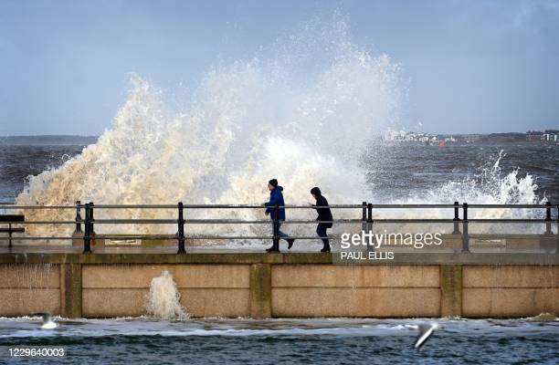 Waves break over a wall separating the marine lake from the sea at New Brighton in north west England on November 16, 2020 as high tide approaches.