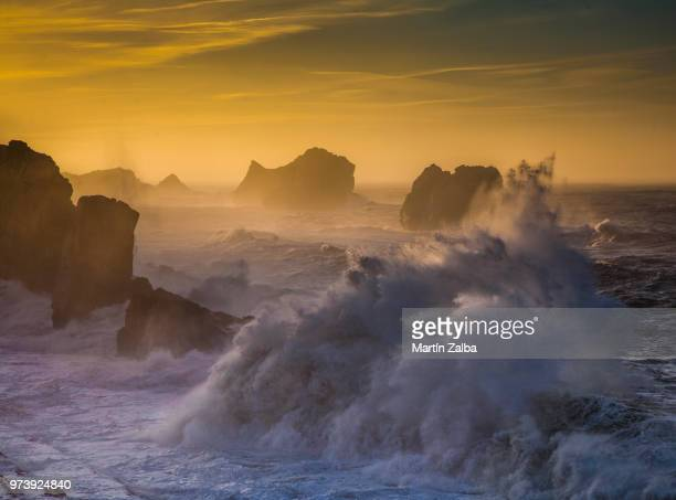 waves breaking against rocks on sea at sunset, liencres, cantabria, spain - カンタブリア ストックフォトと画像