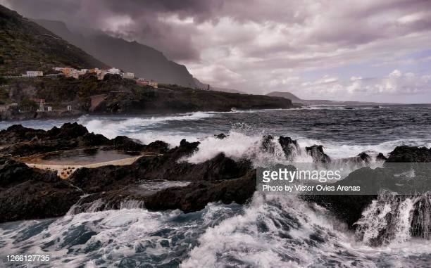 waves breaking against the rock over the natural pools in garachico in tenerife island - victor ovies fotografías e imágenes de stock
