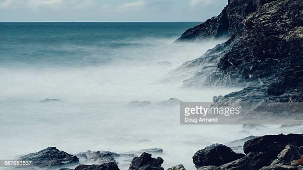 Waves breaking along the shoreline rocks