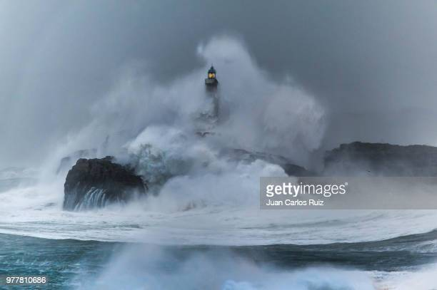 Waves breaking on a lighthouse in Cantabria, Spain.