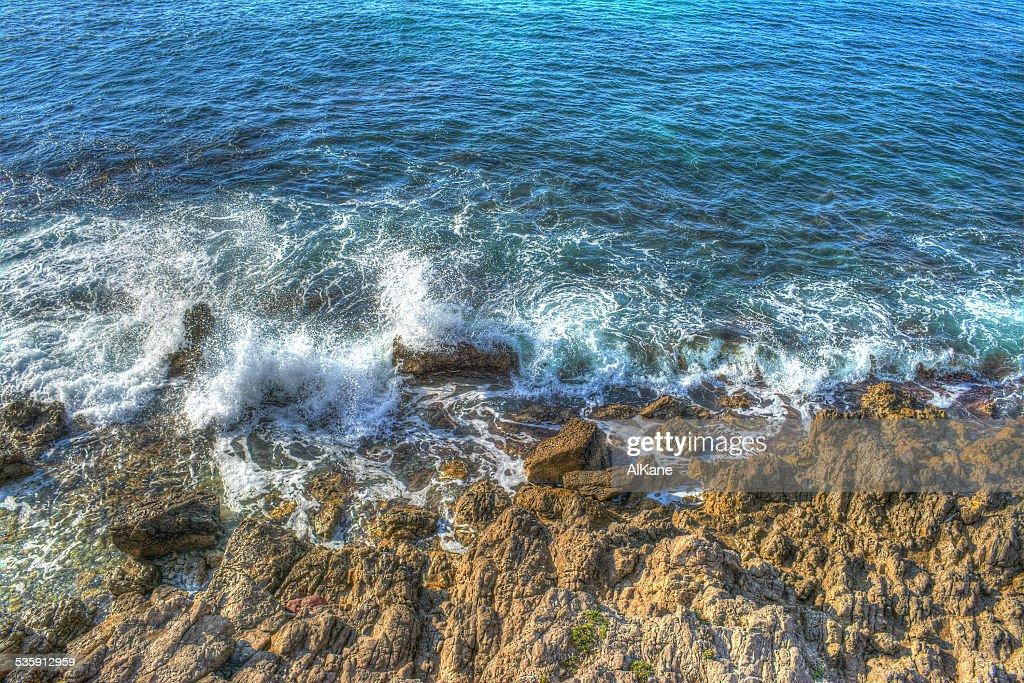 Romper de las olas sobre marrón rocks : Foto de stock