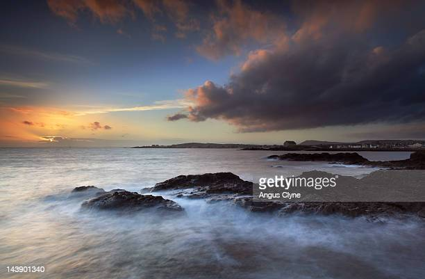 waves breaking on rocky shore at sunset - fife scotland stock pictures, royalty-free photos & images