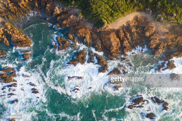 waves breaking onto a rocky shoreline - rocky coastline stock pictures, royalty-free photos & images