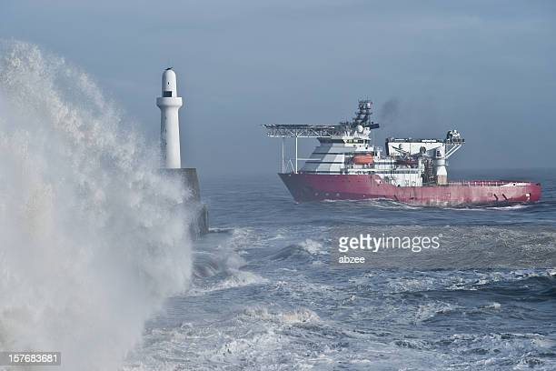 Waves breaking over harbour wall with approaching vessel